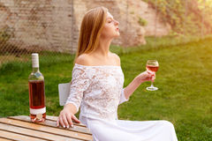 Beautiful woman drinking wine in outdoors cafe. Portrait of young blonde beauty in the vineyards having fun, enjoying a Stock Photos
