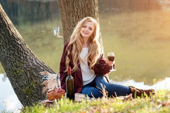 Beautiful woman drinking wine outdoors having picnic in the park. Portrait of young blonde beauty enjoying a glass of Stock Photography