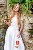 Beautiful woman drinking wine outdoors. Portrait of young blonde beauty in the vineyards having fun, enjoying a glass of Stock Images