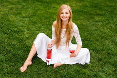 Beautiful woman drinking wine outdoors. Portrait of young blonde beauty in the vineyards having fun, enjoying a glass of Stock Image