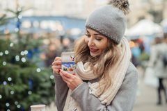 Beautiful woman drinks hot wine on christmas market Stock Photography