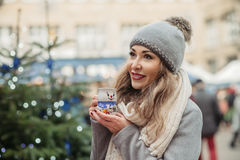 Beautiful woman drinks hot wine on christmas market Royalty Free Stock Image