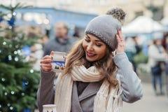 Beautiful woman drinks hot wine on christmas market. Beautiful woman with brown eyes drinks hot wine on christmas market Stock Photo