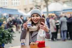 Beautiful woman drinks hot wine and makes a self photo on christ Royalty Free Stock Photos
