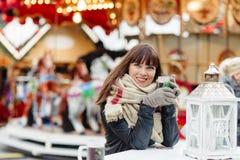 Beautiful woman drinks mulled wine on christmas market. Beautiful woman in scarf drinks mulled wine on christmas market Stock Photo
