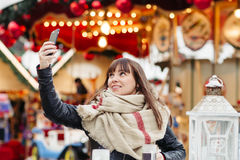 Beautiful woman drinks mulled wine and makes a selfy on mobile p Royalty Free Stock Image