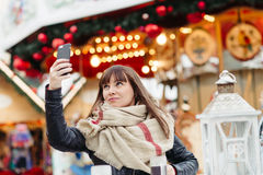 Beautiful woman drinks mulled wine and makes a selfy on mobile p Stock Photo