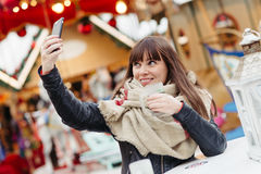 Beautiful woman drinks mulled wine and makes a selfy on mobile p Royalty Free Stock Images