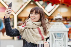 Beautiful woman drinks mulled wine and makes a selfy on mobile p Royalty Free Stock Photography