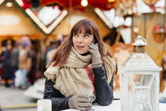 Beautiful woman drinks mulled wine and talk on mobile phone on c Royalty Free Stock Photo