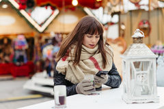 Beautiful woman drinks mulled wine and talk on mobile phone on c Stock Image