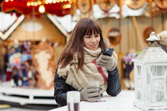 Beautiful woman drinks mulled wine and talk on mobile phone on c Royalty Free Stock Photos
