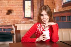 Beautiful woman drinks tea in cafe. Royalty Free Stock Image