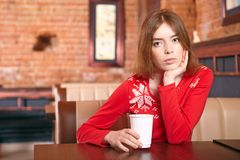 Beautiful woman drinks tea in cafe. Royalty Free Stock Images