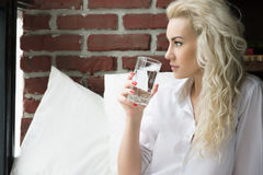 Beautiful Woman Drinks Water in the Morning. Young Woman Drinks Water in Bed Royalty Free Stock Photography