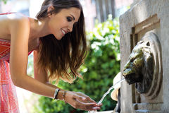 Beautiful woman drinks water from source in summer city park. Stock Photo