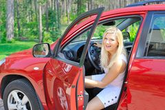 Beautiful woman driver in red shiny car Royalty Free Stock Photos
