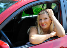 Beautiful woman driver in red shiny car Royalty Free Stock Image