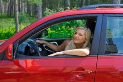 Beautiful woman driver in red shiny car Stock Images