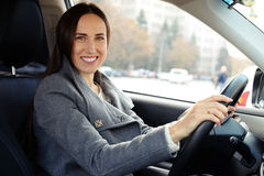 Beautiful woman driving a car and looking at camera Stock Photography