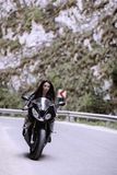 Beautiful woman driving a motorcycle. On a mountain road Royalty Free Stock Photo
