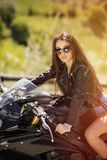 Beautiful woman driving a motorcycle. On a mountain road stock photography