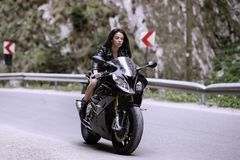 Beautiful woman driving a motorcycle. On a mountain road stock photo
