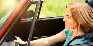 Beautiful woman driving red cabriolet. Smiling beautiful woman driving red cabriolet during sunny day Stock Photos