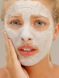 Beautiful woman with dry mud mask, worried Royalty Free Stock Image