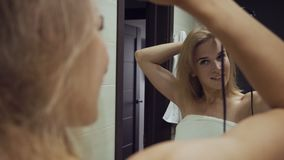 Beautiful woman drying hair with brush dryer after taking shower in bathroom. stock video footage