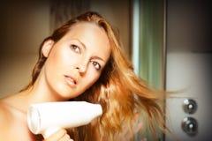 Beautiful  woman drying her hair. Beautiful blonde woman drying her hair Royalty Free Stock Photos