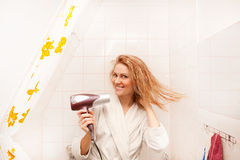 Beautiful woman drying her hair with hairdryer Stock Photography