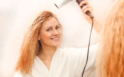 Beautiful woman drying her hair with hairdryer. The beautiful woman drying her hair with hairdryer Royalty Free Stock Image