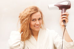 Beautiful woman drying her hair with hairdryer. The beautiful woman drying her hair with hairdryer Royalty Free Stock Photography