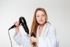 Beautiful woman drying her hair. Isolated on a white background Stock Photos