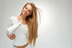 Beautiful Woman Drying Straight Hair Using Dryer. Hairdressing royalty free stock photo