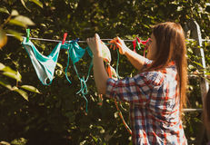 Beautiful woman drying swimsuits on clothesline Stock Image