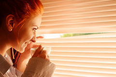 Beautiful woman early in morning with cup of coffee at window Royalty Free Stock Photo