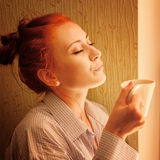Beautiful woman early in morning with cup of coffee at window Stock Images