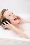 Beautiful woman with earphones in the bath. Royalty Free Stock Images
