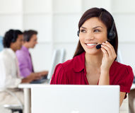 Beautiful woman with earpiece on in a call centre Royalty Free Stock Photo