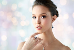Beautiful woman with earring, ring and pendant Stock Images