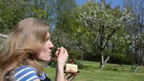 Beautiful woman eat sweet pie cake piece in spring garden stock video