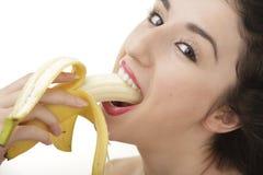 Beautiful woman eating banana. Beautiful sexy woman eating banana on white background Stock Image