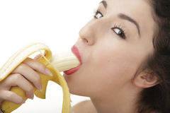 Beautiful woman eating banana. Beautiful woman sucking banana on white background Stock Photo