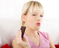 Beautiful woman eating a bar of chocolate Stock Image