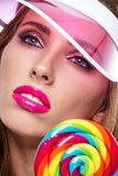 Beautiful woman eating big red lollipop in sun hat. Beautiful woman eating big  lollipop in sun hat on white background Royalty Free Stock Image