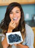 Beautiful woman eating blueberries Stock Photos