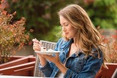 Beautiful woman eating cake. One the terrace stock photo