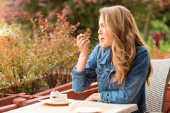Beautiful woman eating cake. One the terrace stock images